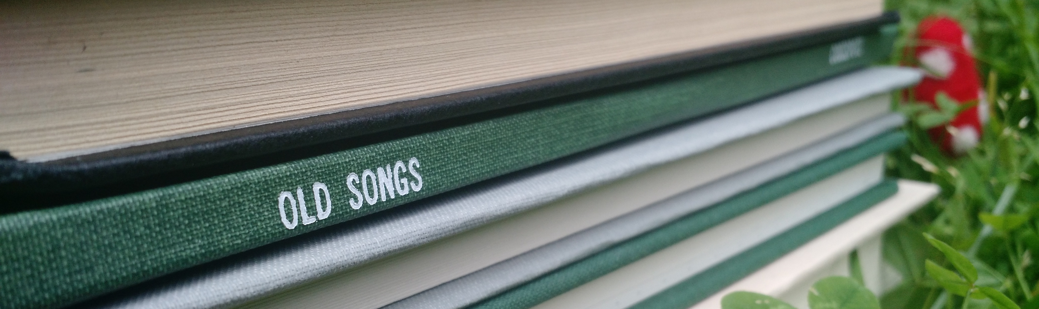 a picture of the spine of Old Songs in a stack of books, with clover and a toadstool in the background